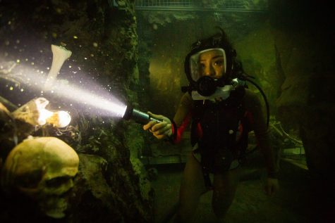 Alex (Brianne Tju) swims into a thin underwater passage in which she finds human remains. Image from the EPK.TV.