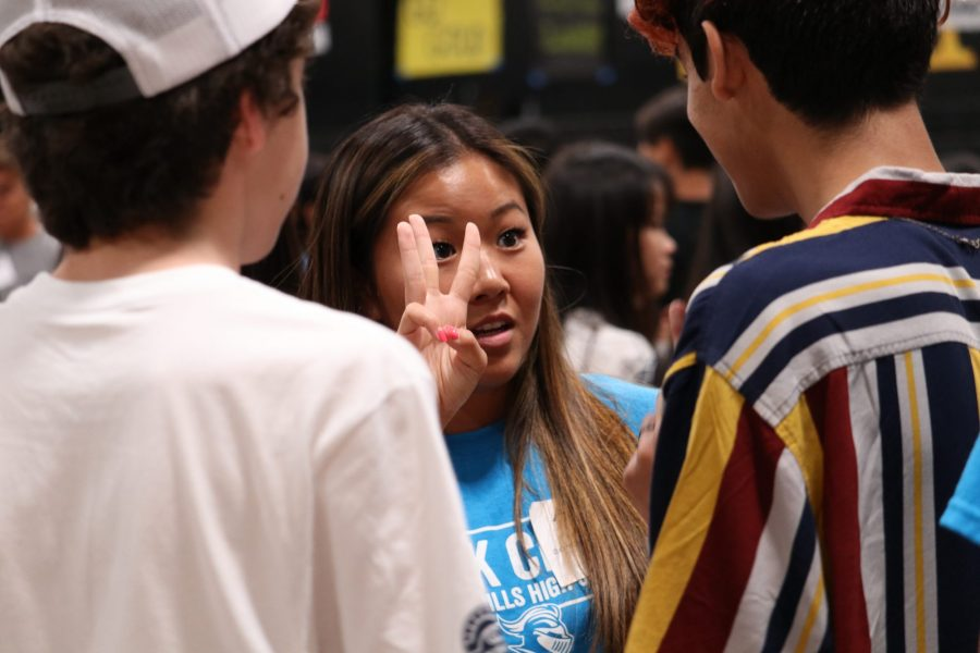 Senior Link Crew leader Aimee Park helps two students find their name tags during the Aug. 6 orientation (Image posted with permission from Julia Hur).