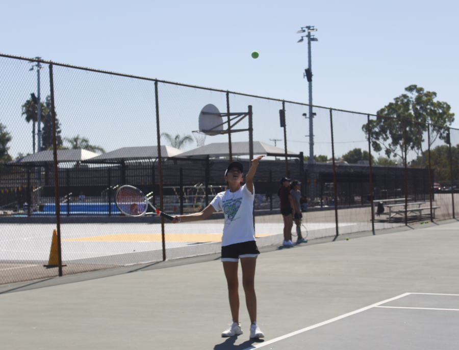 Sophomore Carolyn Tran starts her tennis serve toss during practice at Aug. 14. Photo taken by Accolade photographer Brianna Zafra.
