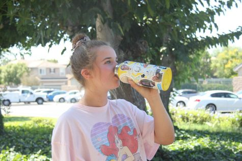Junior Jenna Beining drinks water from her yellow colored Hydro Flask covered in stickers on Sept. 15. Photo taken by Accolade photo editor Megan Shin.