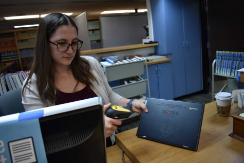 Librarian technician Laura Prompongsatorn scans one of the new Lenovo model Chromebooks on Aug. 13 in the school library. The Chromebooks were distributed to freshmen at the beginning of the school year. (Photo taken by Accolade photographer Paul Yasutake)