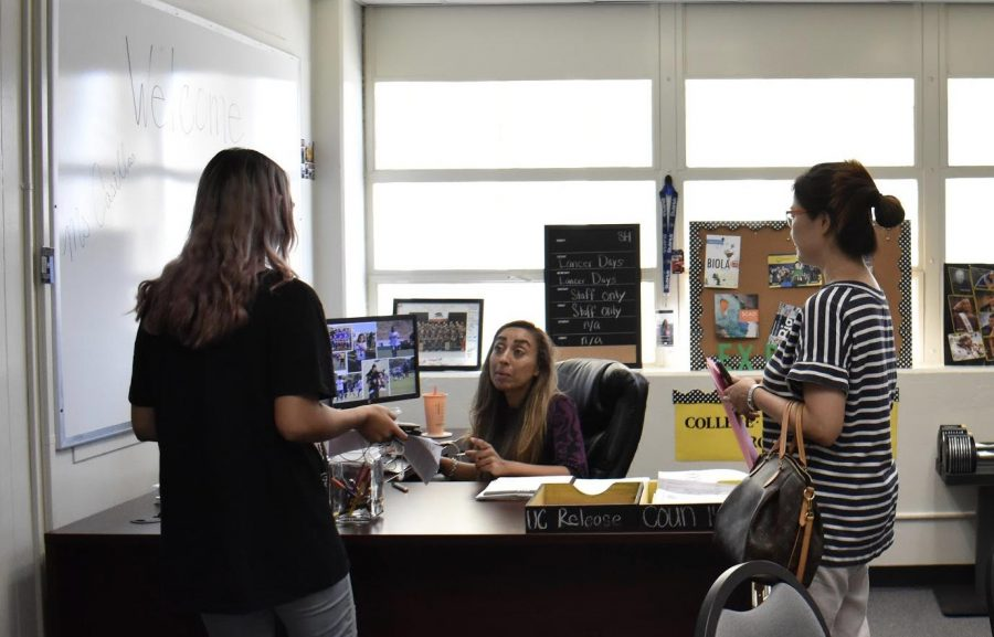 College and Career Center's guidance and counseling technician Evelyn Casillas (center) helps a student and parent gain information on the college application process. (Photo by Accolade photo editor Megan Shin)