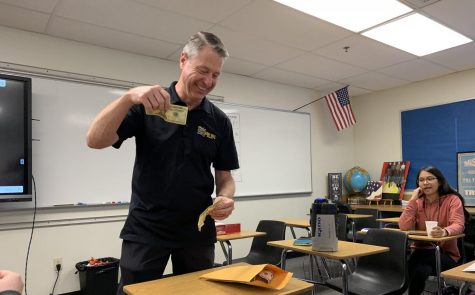 International Baccalaureate Economics HL1 teacher Robert Bradburn holds a $20 and $10 bill before putting the money into an envelope during the Oct. 18 ASB-sponsored