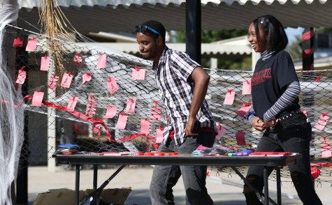 Seniors Branden Elliott (left) and Kourtney Barbour dance to the music in the quad Oct. 29 while helping man the Friday Night Live bean bag toss game as part of the week's Red Ribbon Week festivities. Behind the two is the
