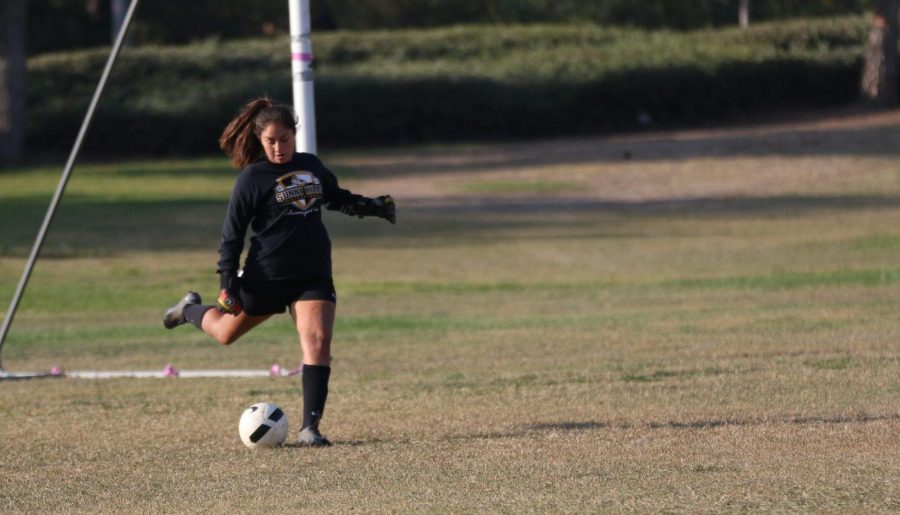 Junior goalkeeper Cil Avila kicks off the soccer ball during a goalkick in practice Nov. 7 at the field next to Hydroflow. Photo taken by Paul Yasutake