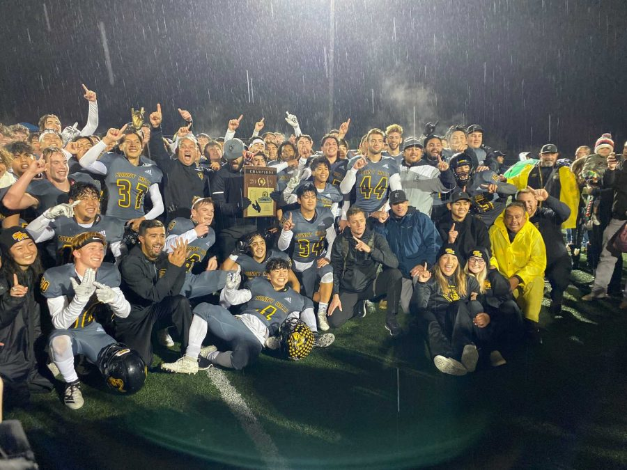The Lancer football team celebrates its first CIF title in 27 years by posing with the championship plaque in the rain Nov. 30 at San Marcos High School stadium. Photo taken by Accolade photographer Paul Yasutake