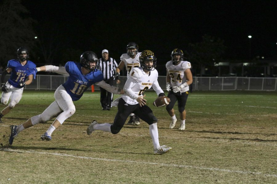 Quarterback and defensive back senior Luke Duxbury escapes from a Bakersfield Christian defender during the CIF State SoCal Regional Division 3-A game Dec. 7 at Bakersfield Christian High School stadium. Photo taken by Accolade photographer Paul Yasutake