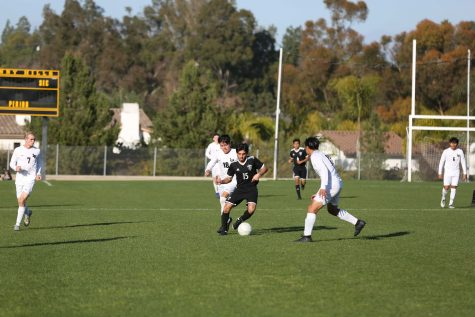 Midfielder senior Brandon Toledo (center) dribbles through a pair of Laguna Hills defenders during Sunny Hills' 2-1 victory over Laguna Hills Feb. 12 at the Sunny Hills field. Photo taken by Accolade photographer Paul Yasutake