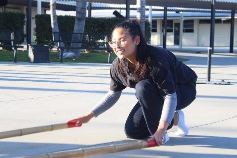 Accolade staff writer and Bayanihan Club member junior Gianne Veluz clicks the two 10-foot-long plastic bamboo sticks in one of her many practices to prepare for the Feb. 6 International Food Faire assembly. Photo taken by Accolade photographer Brianna Zafra.