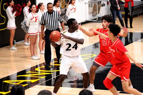 Sunny Hills boys basketball forward senior Emmanuel Seddoh (left) searches for a teammate to pass the ball to while being double-teamed during the second quarter of the Lancers' 72-65 victory at home over Fullerton Feb. 4. Photo taken by Accolade photographer Brianna Zafra