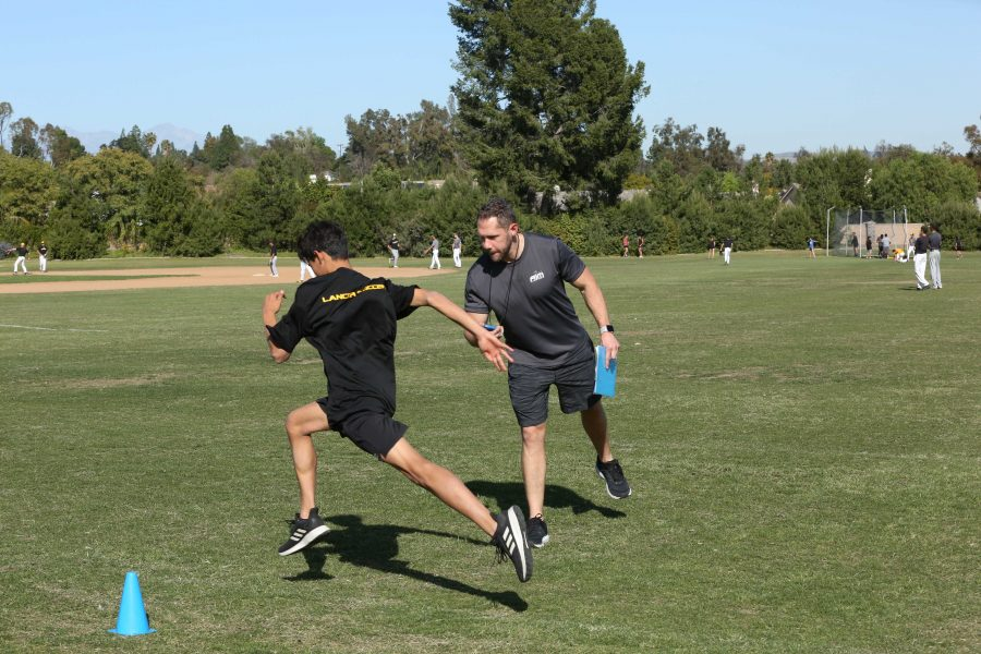 Athletes in Motion instructor Jason Hitchens (right) points junior Joshua Bustamante towards the next training station on Feb. 27 at the SH field. Photo taken by Accolade photographers Paul Yasutake