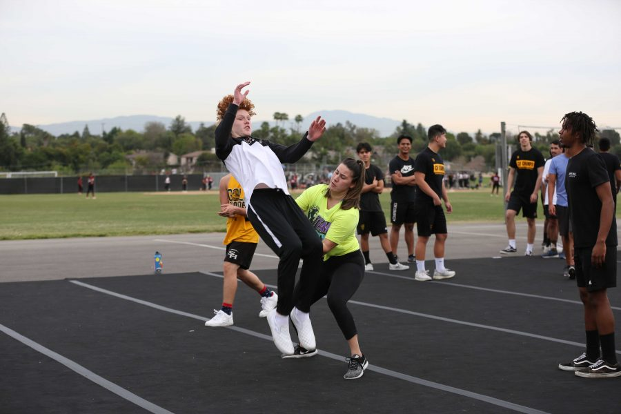 Cheer coach Lizzy Mejia (right) helps basketball player and male cheerleader sophomore Jacob Dedeaux perform a backflip as male cheerleaders watch in the background on the Sunny Hills blacktop during a Feb. 27 practice. Dedeaux and 18 other male athletes will show off their skills in the March 13 assembly. Photo taken by Accolade photographer Paul Yasutake