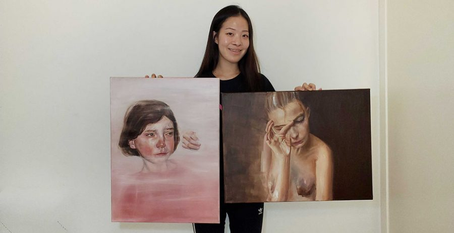 Junior Grace Park holds up her two award-winning paintings -- Rotten (left) earned her a first-place $100 check and Hide netted an honorable mention $10 check, both of which she has since cashed -- that she entered in the 34th annual Fullerton Joint Union High School District Education Art Show. Although the art show was scheduled to begin March 30, it was canceled because of the COVID-19 pandemic. District art show organizers were able to send winners their awards as the event was judged before the exhibit took place. Image used with permission from Grace Park.