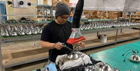 Senior Phillip Kim is shown hot gluing wires to headlights for commercial vehicles and airport signals under a fan to speed up the drying process. Image used with permission from Phillip Kim.