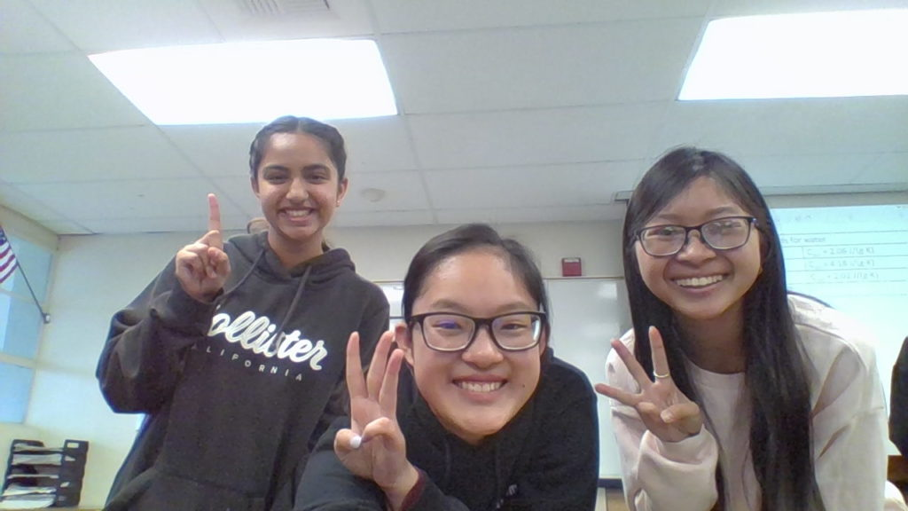 Junior Hope Li (center) gets her friends in her sixth period Honors Chemistry class to hold up their fingers to signify the number 133 on the 133rd day of school March 13, in Room 112. Li started collecting images of a tally of each day of the school year as a time capsule project at the start of the 2019-2020 school year. Despite school closure because of the coronavirus pandemic announced that day, she has continued with it through the last day of the spring semester.
