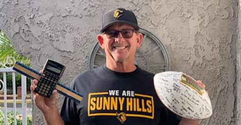 Larry Allen holds in one hand a calculator and ruler to represent the math classes he has been teaching at Sunny Hills, while his other hand holds a football signed by his 2018 Freshman City Championship players. Image posted with permission from Aurora Allen.