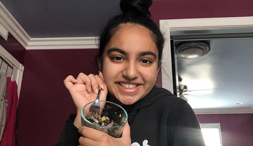 Nevya Patel uses her own smarthpone to capture her holding a bowl of spiced vegetables, including onions, spinach and corn and black beans, which she eats as her healthy snack. She incorporated the beans to make sure she is still receiving protein because of the lack of meat intake.