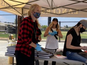 With blue gloves and face mask covering her mouth, math teacher Nicole Knutson (left) gets ready to hand off another yearbook to the next person pulling up to the drive-through distribution lane on the parking lot near the Performing Arts Center Tuesday afternoon. Yearbook adviser Lindsay Safe (center) supervises the operation while math teacher Mariam Tan uses a chromebook to confirm the names given to them. Photo taken by Accolade opinion editor Hope Li.