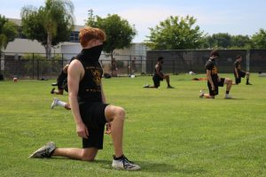 Defensive back rising junior Dane Soaper kneels while stretching following a June 23 practice on the Sunny Hills baseball field. The SH football team had been preparing to defend its 2019 CIF-SS Division 8 title when the Orange County Department of Education opened schools for sports summer workout sessions but now must wait until January 2021 to play under Friday night lights again.