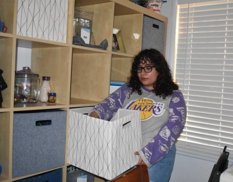 Senior Aaliyah Magana puts her binder away in her cubic box in a six-by-six foot bookcase, a part of her at-home learning system for the new school year, after the online school day has ended.