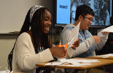 Then-junior Ella Eseigbe (center) cuts paper during a classroom simulation of a tent-making company in her IB Economics Higher Level 1 class last November. The class' corresponding exam is just one of the many assessments that IB is modifying for the 2020-21 school year.