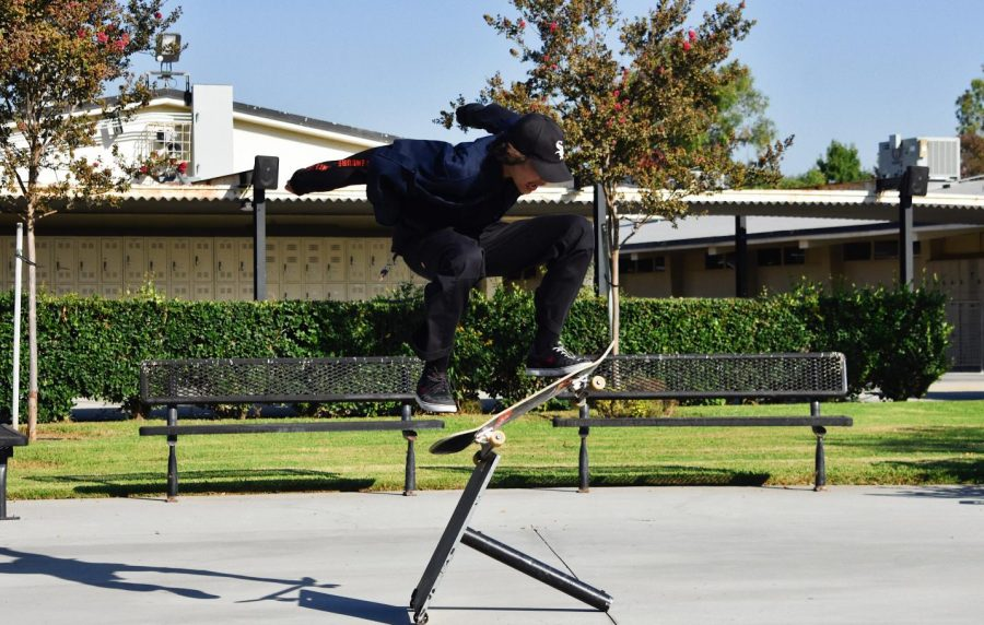 While the Sunny Hills campus is devoid of students until it reopens to hybrid learning, some like sophomore Michael Ramirez have been coming out to the quad after school hours to practice their skateboarding skills. Here, Ramirez uses a broken umbrella base as a prop to hop over while riding his skateboard.