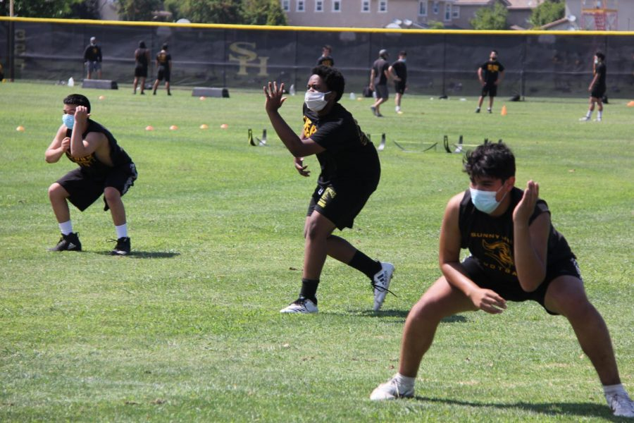 Football players train while socially distanced June 23 before an athlete encounter with COVID-19 shut down practices two months later.