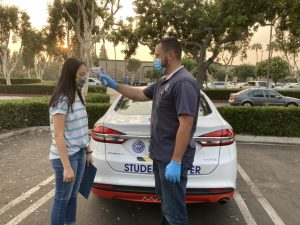 Before her Sept. 15 AAA driving lesson, senior Hope Li (left) dons a face mask as her instructor, Daniel Pedraza, takes her temperature in front of the AAA student driver car. Li has been taking lessons since July, following coronavirus precautions like wearing gloves in the car and sitting on a plastic seat cover.