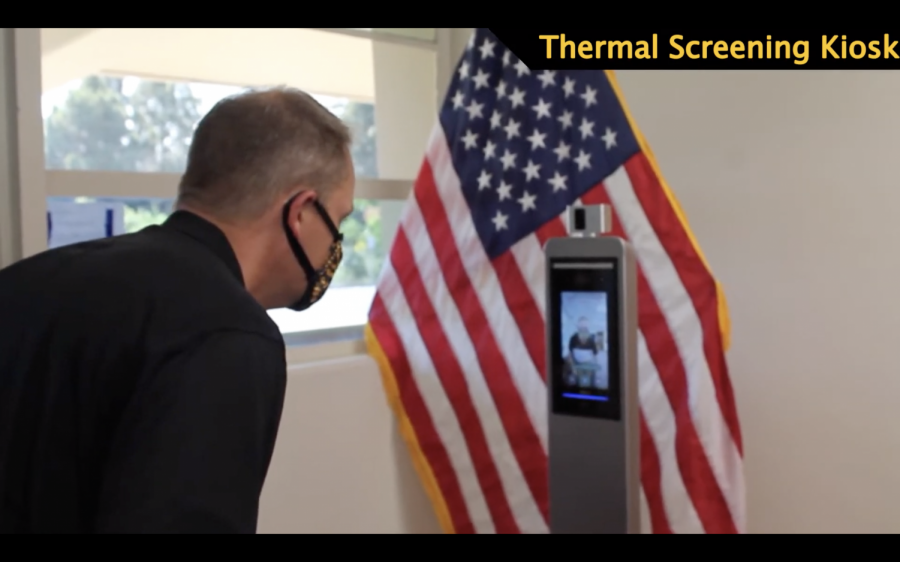 Principal Allen Whitten demonstrates scanning his temperature at one of the school
