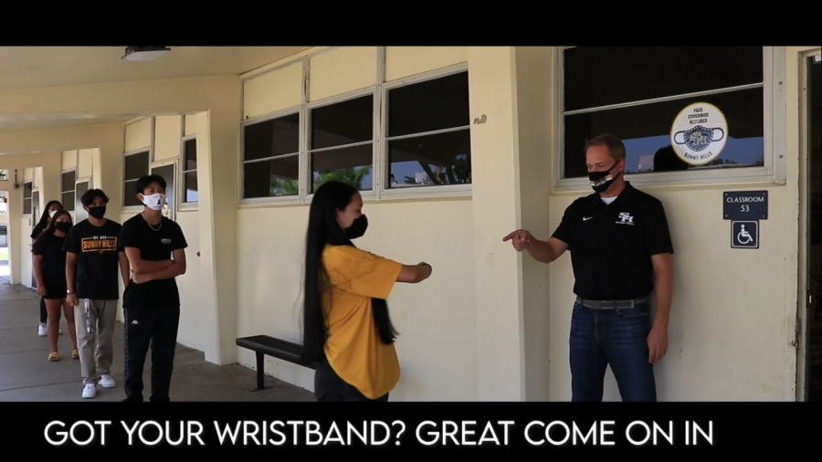A skit in the video shows principal Allen Whitten checking to see if students are wearing their required wristband, which signifies that a student has a temperature below 100 degrees and is allowed to be on campus for that day.