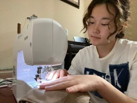With her sewing machine, junior Violet Kim makes a denim bag for her first collection released Sept. 12. Kim is wearing a shirt from her collection as well.