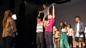 Theater teacher Amanda Gieser (left) glances at one of her performers being lifted up by cast members of 2018's