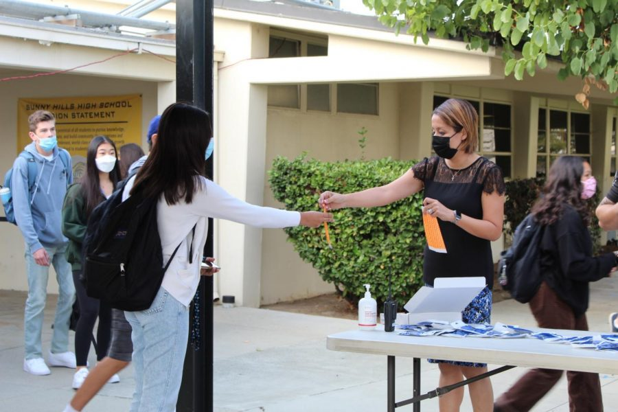 Assistant principal Hilda Arredondo hands an orange wristband to a student before first period on Nov. 2.