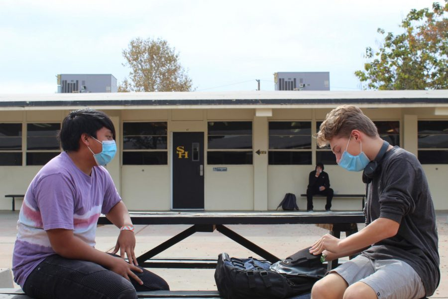 Sophomores Jeremiah White and Roman Ruedas sit on opposite ends of a bench between the 40s and 60s wings while holding a conversation on Nov. 2. For many students, Nov. 2 and Nov. 3 — the respective first dates for Cohorts A and B under the new hybrid schedule — were the first days in nearly eight months that they could talk to their friends in-person again.