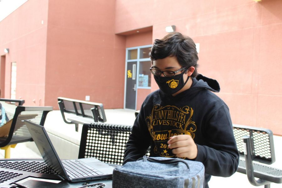 Senior Benicio Tristan uses his chromebook on the tables next to the cafeteria while following COVID-19 health guidelines on Nov. 5 during break, which comes after third period in the new hybrid learning schedule.