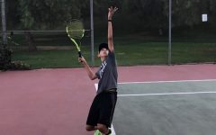 Sophomore Owen Taylor smashes a serve at the San Juan Courts during practice.
