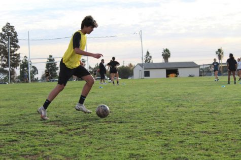 Center defensive midfielder junior Michael Franco guides the soccer ball during practice on the practice field on Dec. 8.