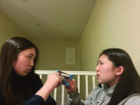 Sisters junior Michelle (left) and freshman Irene Sheen haggle over a Choco Pie snack, one of many tiffs they
