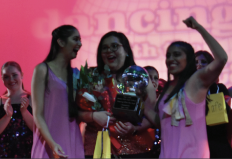 Math teacher Christian Bueno (middle) holds a bouquet of roses and the Dancing with the Staff trophy on Dec. 8, 2017. The annual fundraiser for the dance program would have reached its 10th year had it not been for the coronavirus pandemic. The event was replaced with a drive-in at the farm parking lot where the audience watched video dance performances.