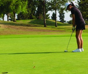 Then-freshman Hannah Kim lines up her shot as she tries to sink her ball into the hole during an August 2016 practice at the Westridge Golf Club in La Mirada. Boys and girls golf head coach Scott Enrico will hold tryouts to see how many he can a dd to his active roster for both squads today, Dec. 2, at 4 p.m. at the same location.