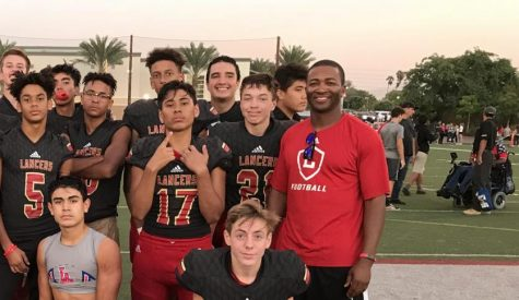 New athletic director Paul Jones (right) stands next to members of the Orange Lutheran freshman football team after a game. Jones held the athletic director position at Orange Lutheran for six years before moving to Sunny Hills.
