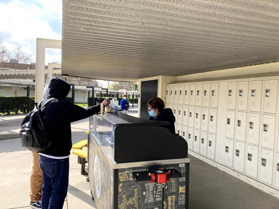 A student receives a free school breakfast meal during break beside the 70s and 90s building on Feb. 16, the first day of hybrid instruction since December 2020.