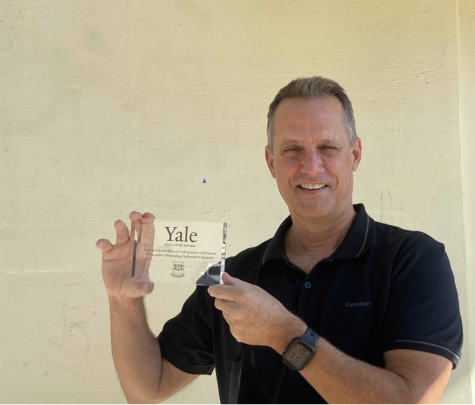 Art teacher and International Baccalaureate coordinator Brian Wall holds up the 2020 Yale Educator Award after receiving it in the mail last September.