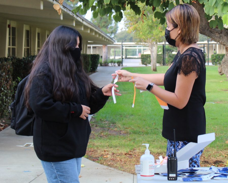 Assistant principal Hilda Arredondo (right) gives a wrist band to a student on the first day of hybrid learning last November as part of the school's health and safety protocols. The same procedure will be followed Tuesday as the campus will be opened for the first time in 2021 after trustees for the Fullerton Joint Union High School District had unanimously agreed to do so during their Feb. 2 emergency meeting.