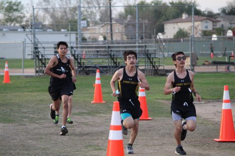 Masks in hand, twin brothers and cross country runners David (center) and Sergio Perez (right) race toward the finish line Feb. 3 on the Sunny Hills track, where the first sports event of the school year was held after the coronavirus pandemic had shut down all previous athletic competitions since last March. The Lancers boys cross country team -- the only SH squad with enough athletes in attendance to compete -- defeated the runners from Buena Park High School by a three-point margin.