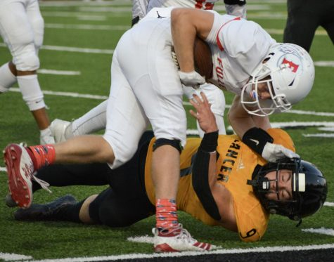 Linebacker senior Carson Irons (bottom) falls down while tackling Fullerton quarterback senior Cameron Williams during the first quarter of the Lancers