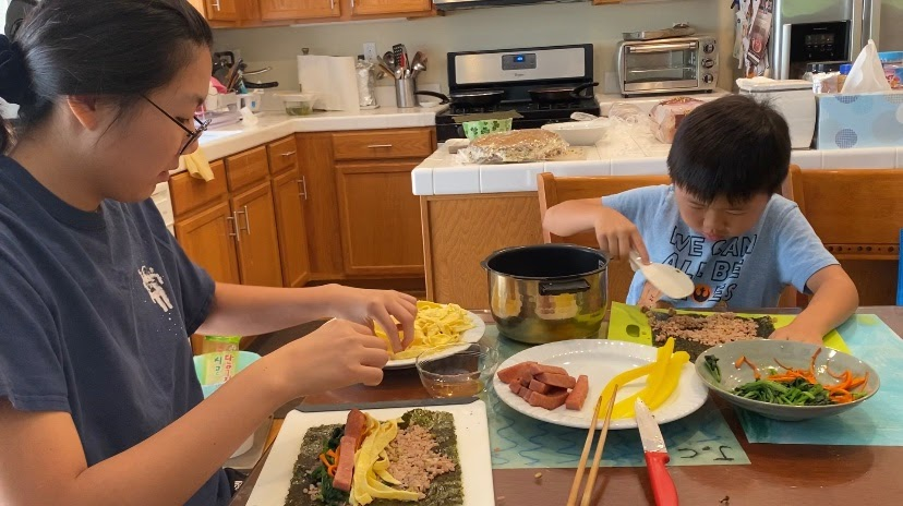 Jaimie Chun (left) and her 7-year-old brother make gimbap, a Korean dish with cooked rice, eggs, spam, spinach and pickled radish. During the coronavirus pandemic, the two shared this meal last summer.