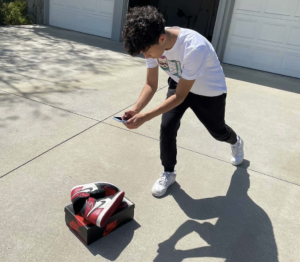 Colin Lee takes a picture of sneakers on top of a shoebox in his normal backdrop of a concrete ground in the front of his house to post on his Instagram on April 21, 2021.