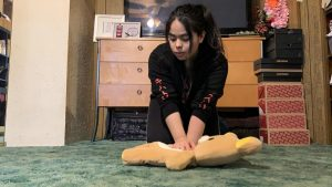 Senior Jessica Garcia demonstrates CPR chest compressions on one of her stuffed animals as a replacement for a dummy. Like all seniors, Garcia had to video record her practicing hands only CPR and submit the video for review by assistant principal Hilda Arredondo to fulfill a state-mandated graduation requirement.