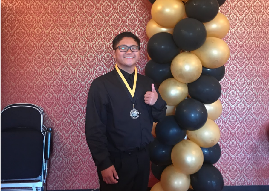 Then-freshman Roy Datuin smiles with black and gold balloons at the 2019 Lancer Awards in Fullerton Union High School's auditorium. Datuin won a Lancer Award in the math department.